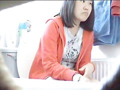 Cute Chinese girl in bathroom on toilet
