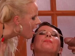 Two women are kissing each other. a guy begins to piss over their faces and into their mouths. th...