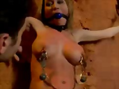 Busty blonde chained to wall mouthgag...