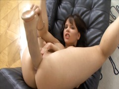 Brunette fucks herself with a big beige dildo