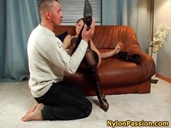 Seductress in boots and stockings kisses him