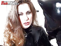A slave dressed in latex catsuit teases