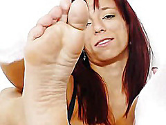 Redhead gives stirring footjobs to dildo