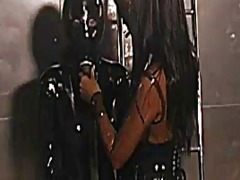 Futuristic latex lesbians have fun with slave in a cage