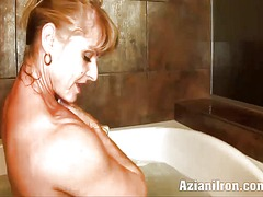 Female bodybuilder flexes and washes ...